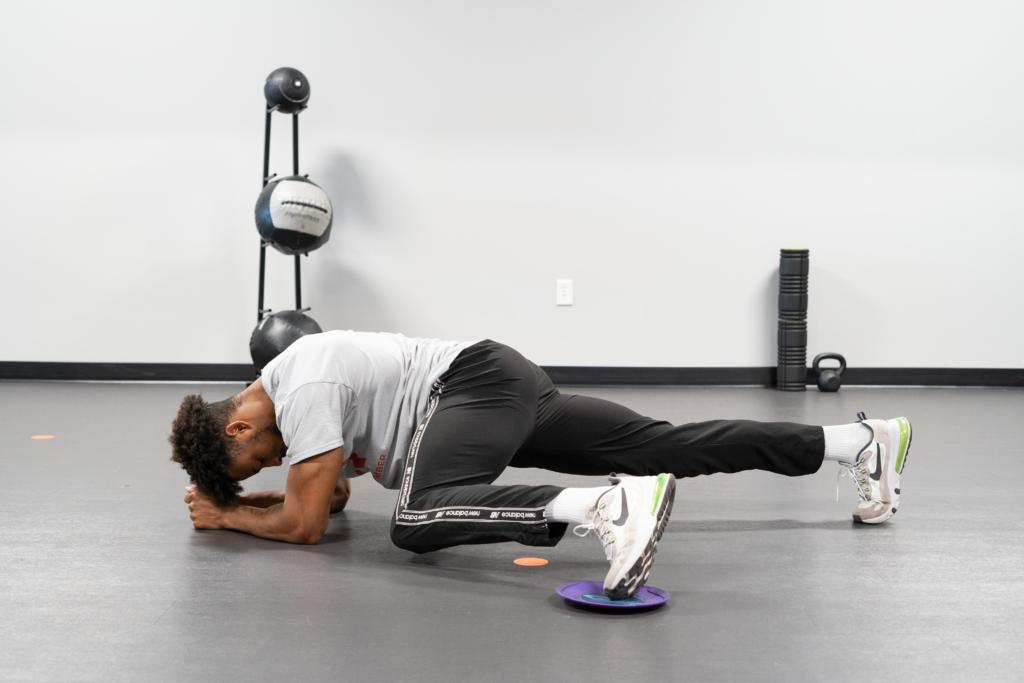 man doing sliding plank crunch