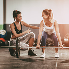 trainer helping woman lift barbell
