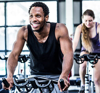 man riding an indoor bicycle while smiling