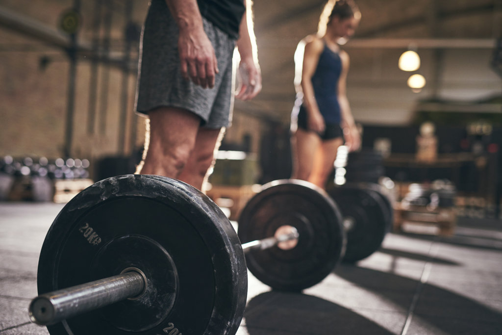 man and woman ready to pick up weights