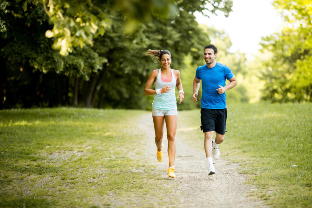 man and woman run in the woods