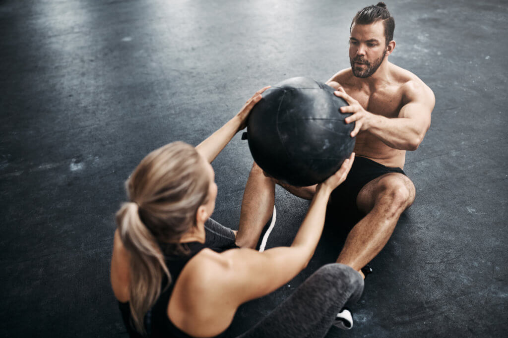 man and woman passing medicine ball back and forth