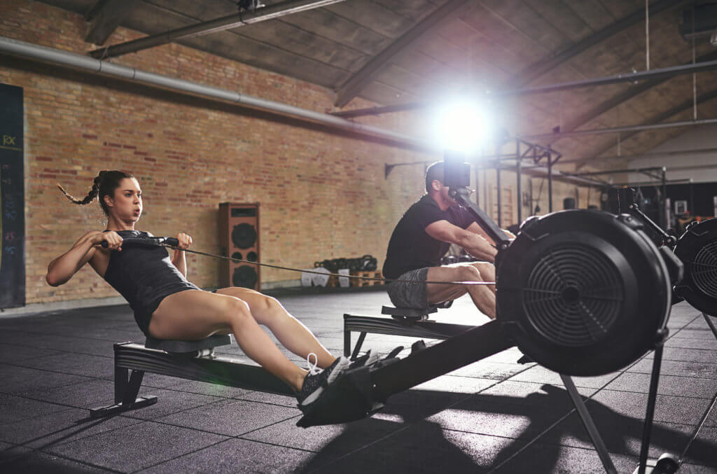 man and woman using a rowing machine