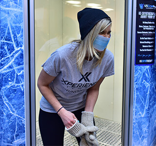 woman standing outside whole-body cryotherapy chamber