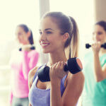 woman holding dumbbell smiling
