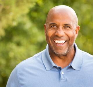 man smiles outdoors