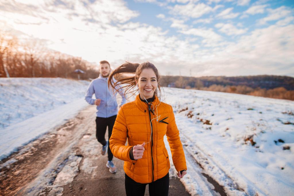 two people run outside in winter