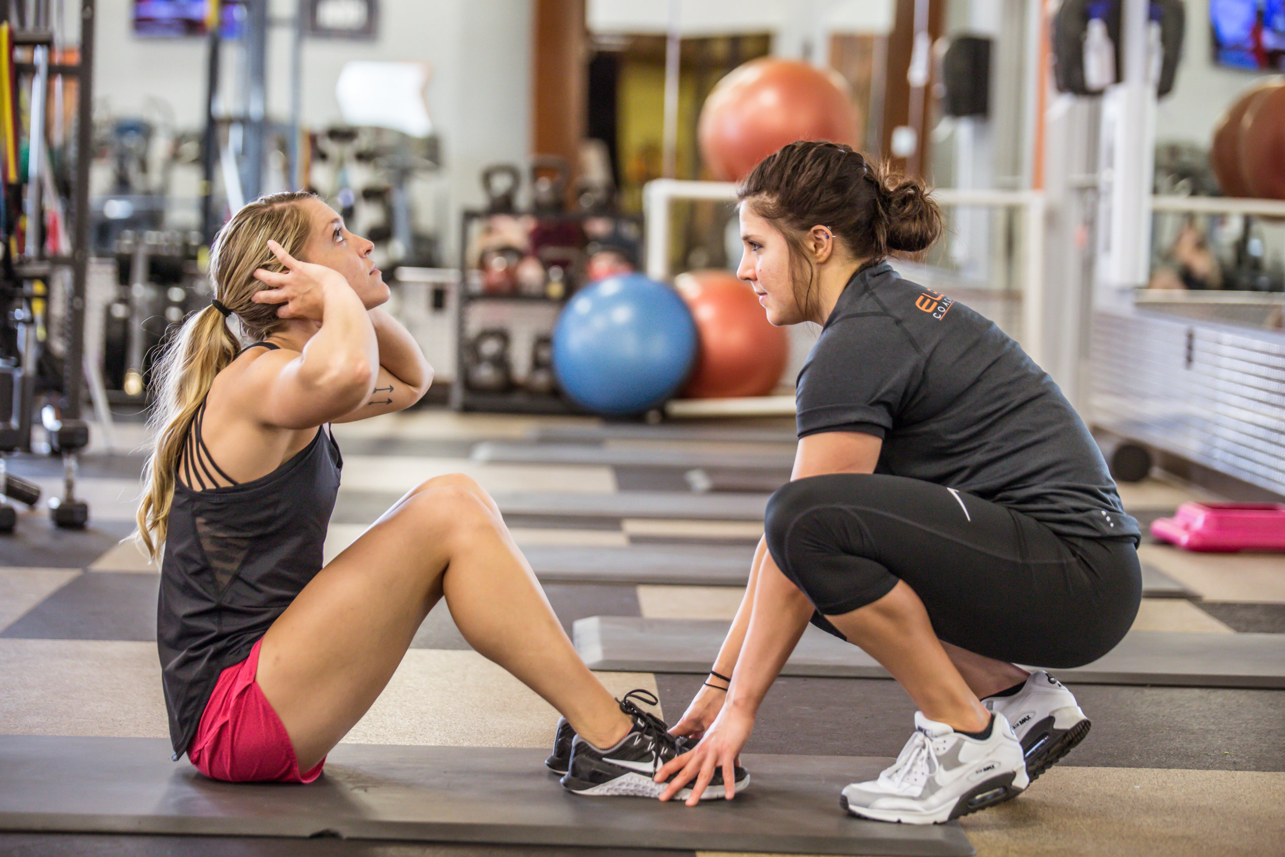 woman doing sit up with trainer