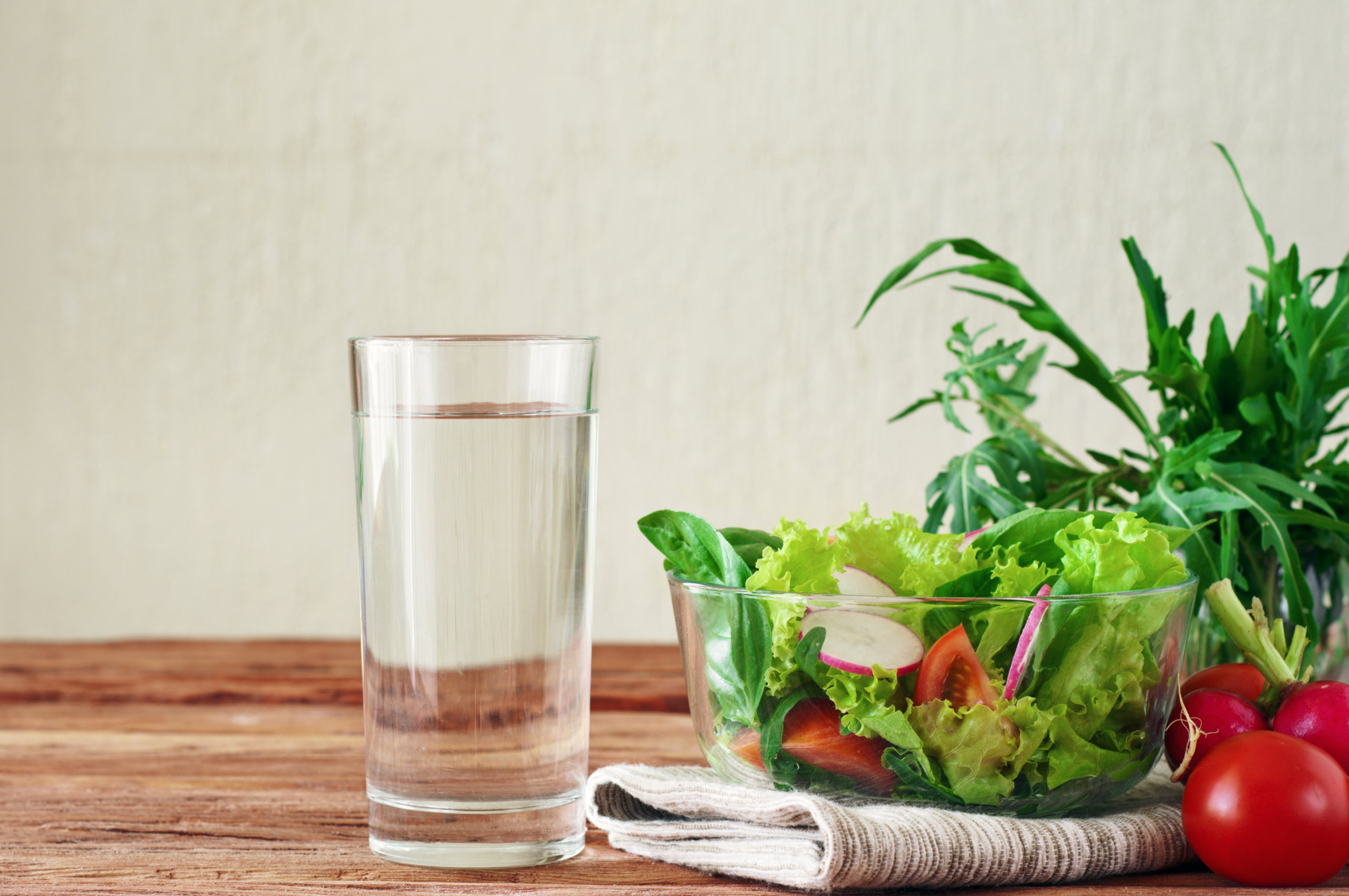 glass of water on table next to salad