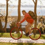man riding bike wearing backpack