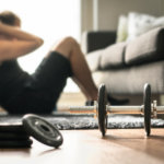 man doing sit up in living room next to dumbbell