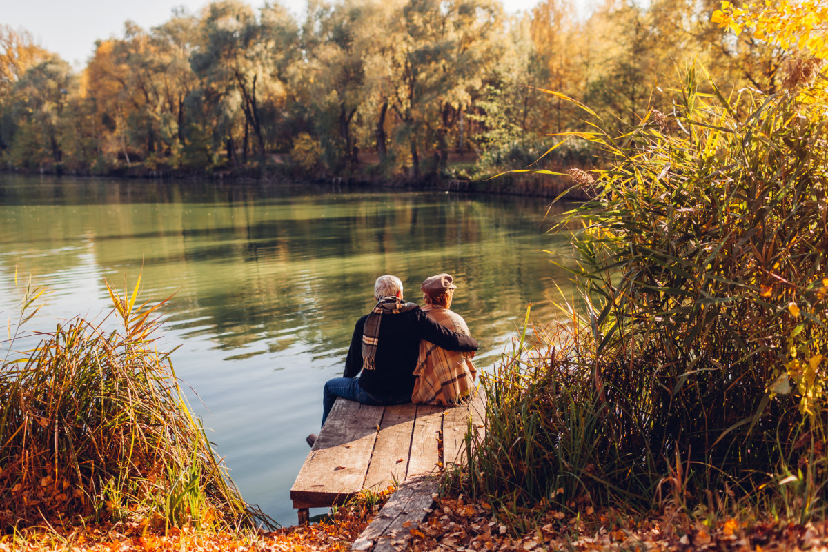 couple sitting on bench by a lake in fall