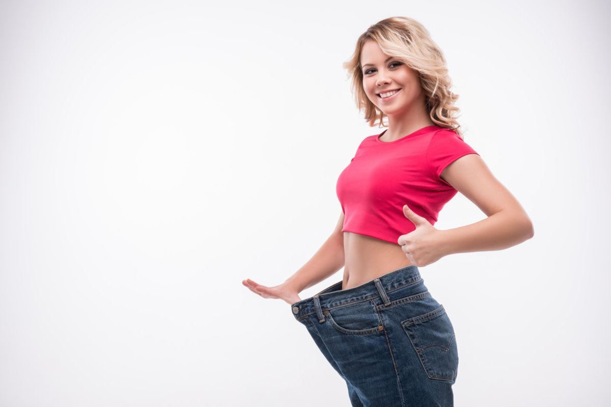 woman in pink shirt wearing big pants after weight loss